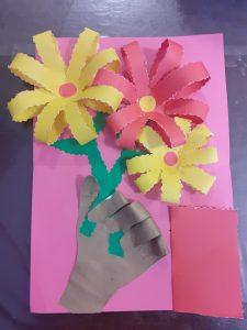 na rozowy tle ręka trzymająca 3 kwiaty - platki zewnętrznych kwiatow maja kolor żółty z różowym środkiem i czerwony na środku, z prawej na dole, kartka z ukrytym napisem dla mamy
