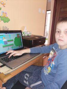 chłopiec z prawej strony ekranu patrzy przed siebie klikając ręką po klawiaturze, na monitorze gra, którą stworzył na kursie