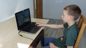 chlopiec przy laptopie, gra w grę