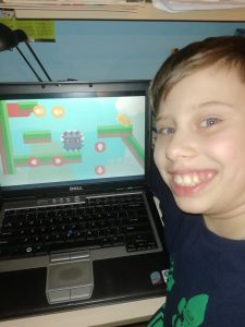 chłopiec z lewej strony uśmiechający się w aparat w tle laptop z gra